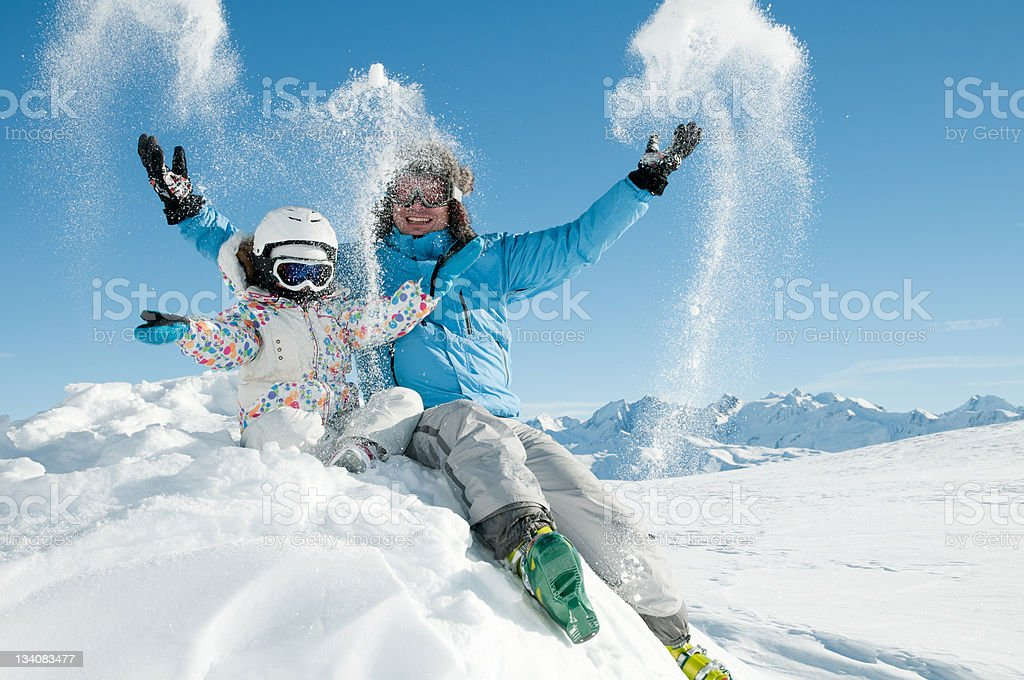 Child and adult happily playing in snow in full winter gear royalty-free stock photo
