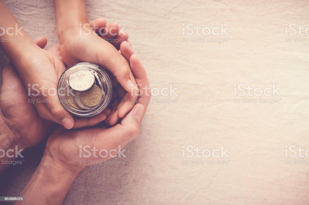 child and adult holding money jar, donation, saving concept stock photo