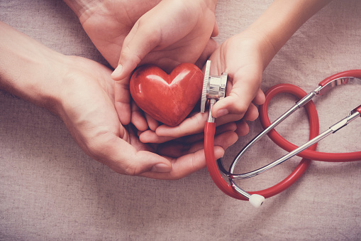 Child And Adult Holding Red Heart With Stethoscope Heart Health Health Insurance Concept — стоковые фотографии и другие картинки Австралия - Австралазия