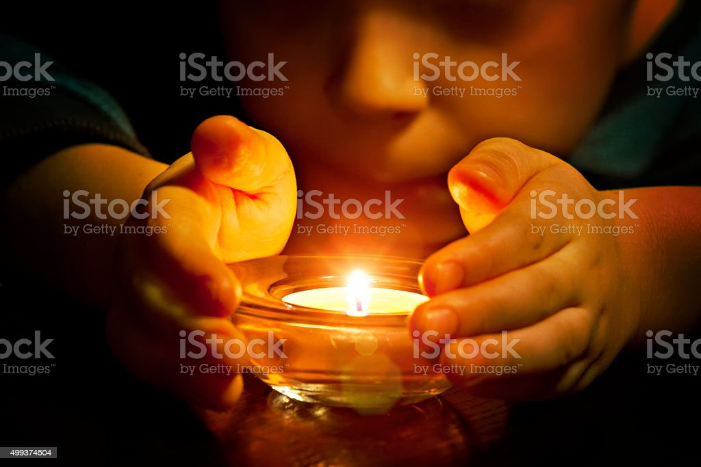 Child and candle light stock photo