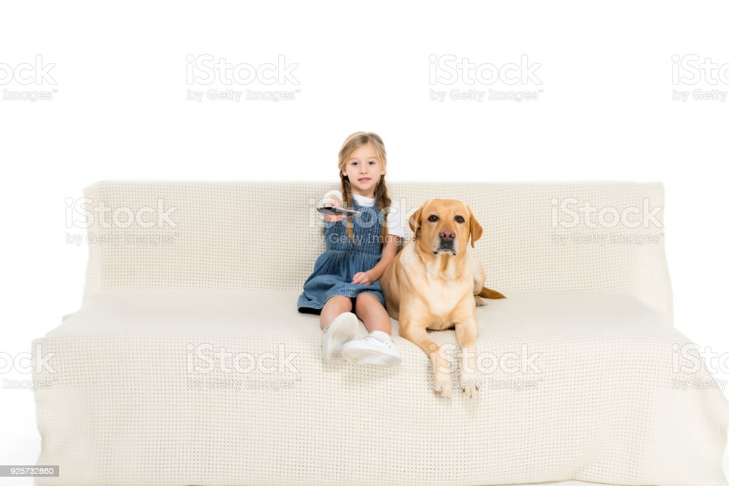 child and dog watching tv on sofa, isolated on white stock photo