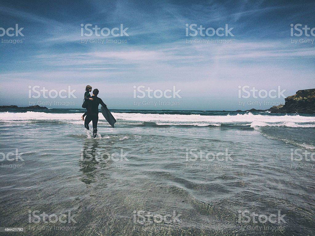 Child and father boogie board together in ocean stock photo