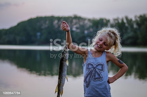 adorable little girl with fish at the pond at the sunset