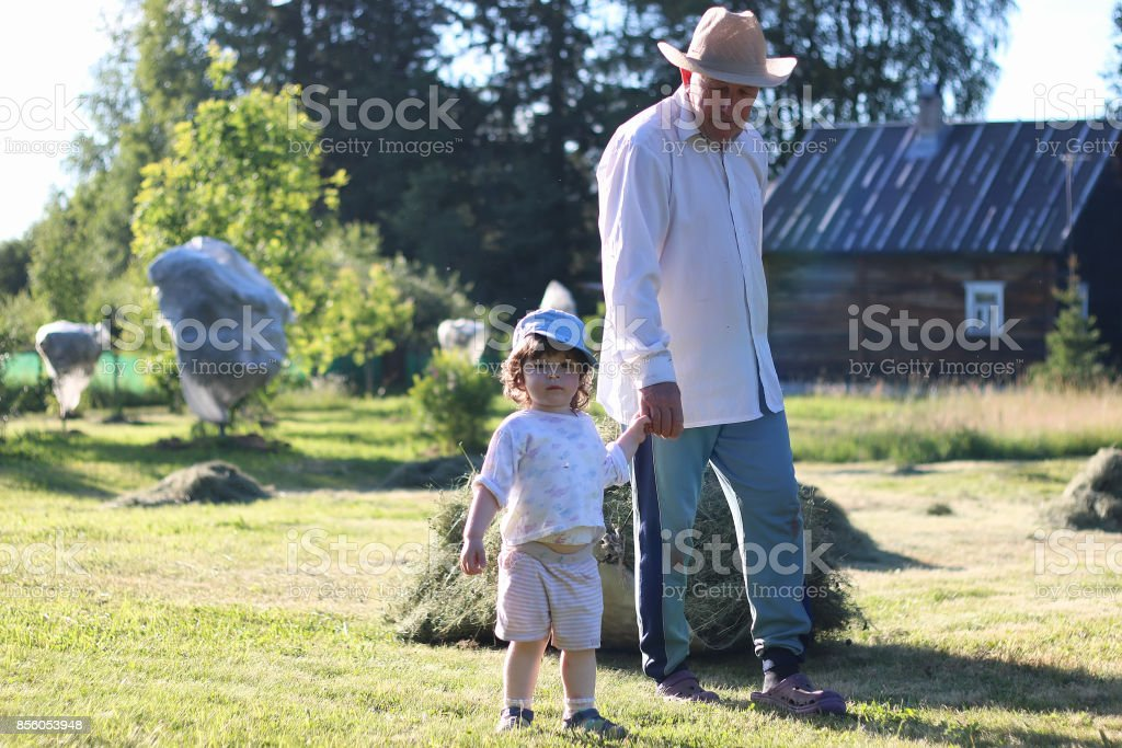child and grandfather harvested hay stock photo