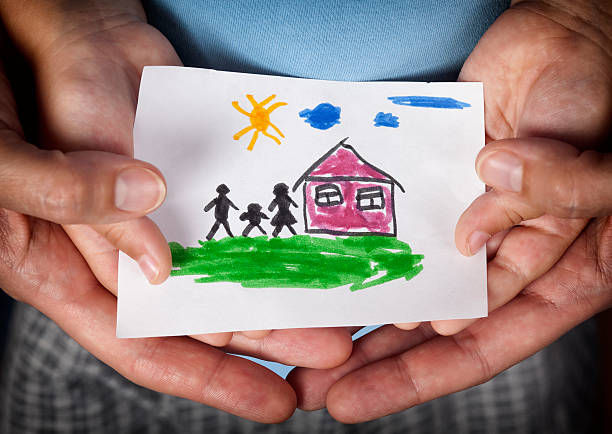 child and his mom holding a drawn house with family - kids drawing stok fotoğraflar ve resimler
