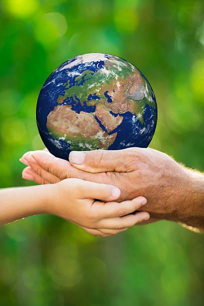 Criança e homem segurando a terra nas mãos - foto de acervo
