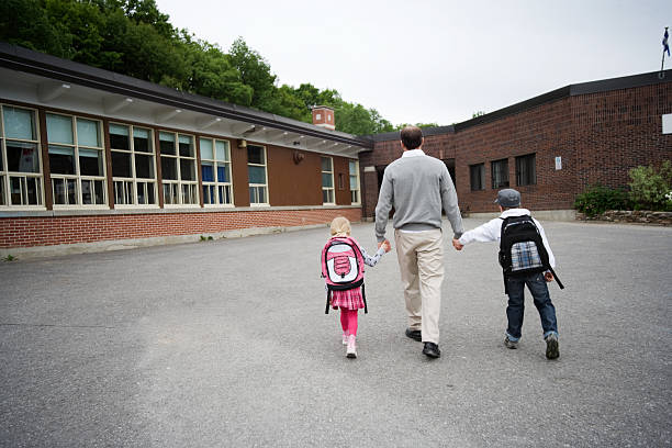Child and Man Walking to School stock photo