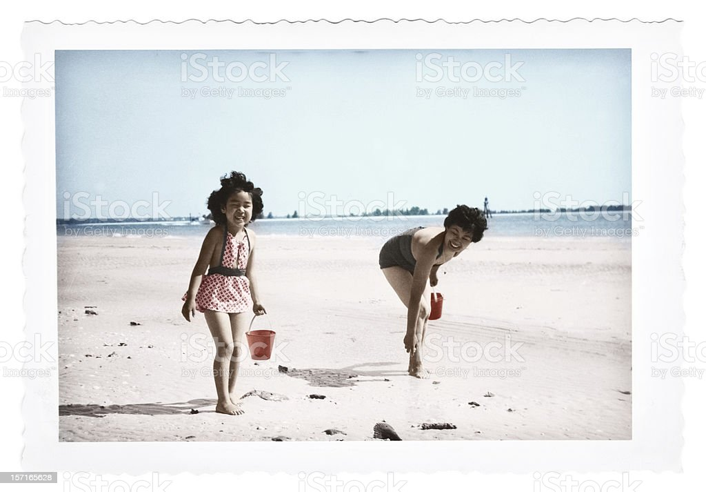 Child and Mother Picking Up Shells stock photo