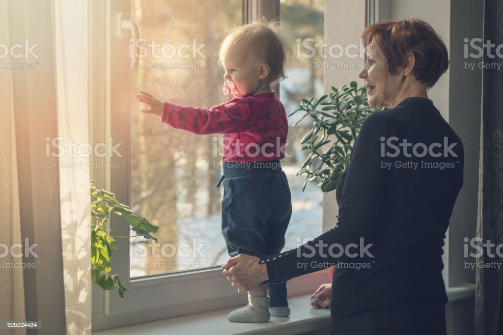 child and nanny spending time together at home looking through the window stock photo