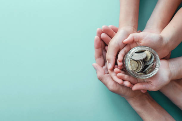 child and parent hands holding money jar, donation, saving, family finance plan concept - financial planning stock pictures, royalty-free photos & images
