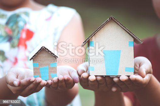 istock Child and parent holding paper house in hands as real estate and family home concept 966783002