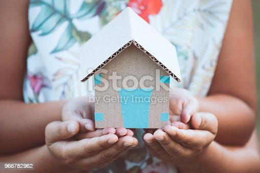 istock Child and parent holding paper house in hands together as real estate and family home concept 966782962