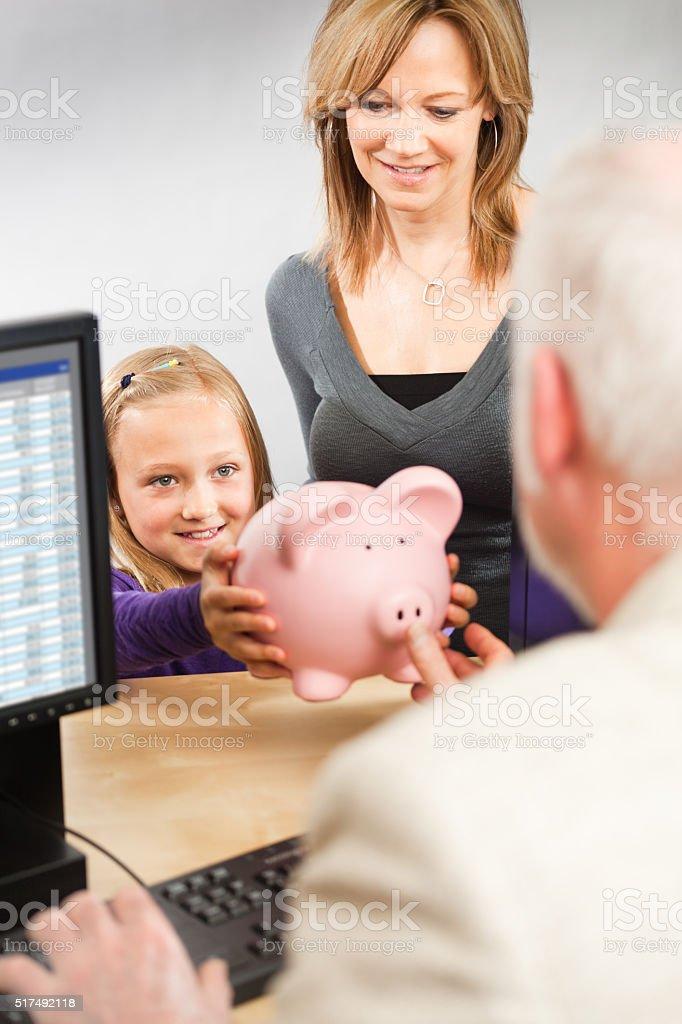 Child and Parent Taking Saving to Retail Bank Teller Counter stock photo