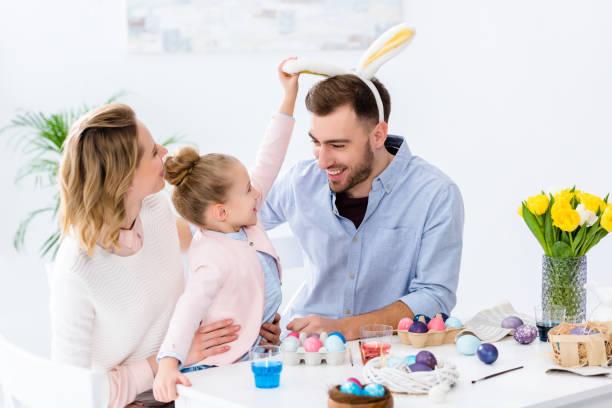 criança e os pais brincando com orelhas de coelho por tabela com ovos de páscoa - familia pascoa - fotografias e filmes do acervo