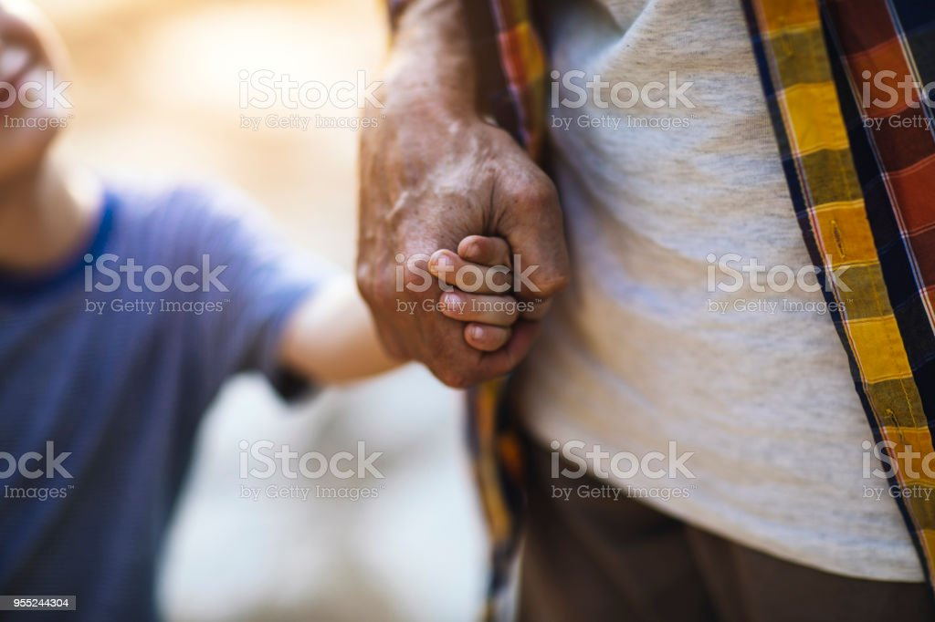 Child and senior adult holding hands stock photo