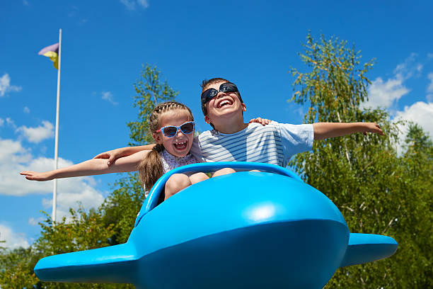 child and woman fly on airplane attraction in amusement park stock photo