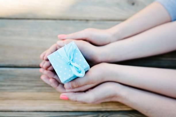kind und frau hält kleine geschenk-box - besondere geschenke stock-fotos und bilder