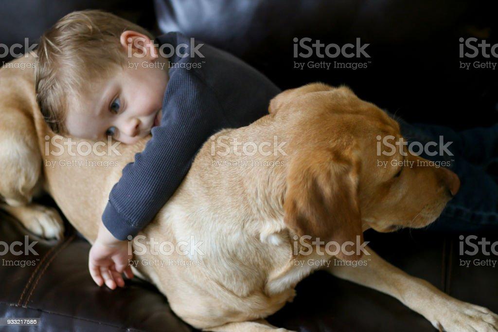 Kind und gelbe Labrador gemeinsam entspannen – Foto