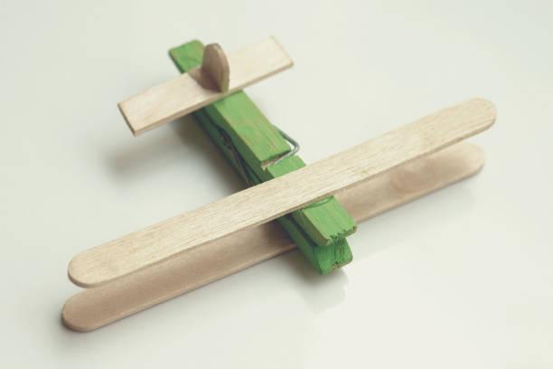 Child artwork, popsicle stick made plane on plain background. stock photo