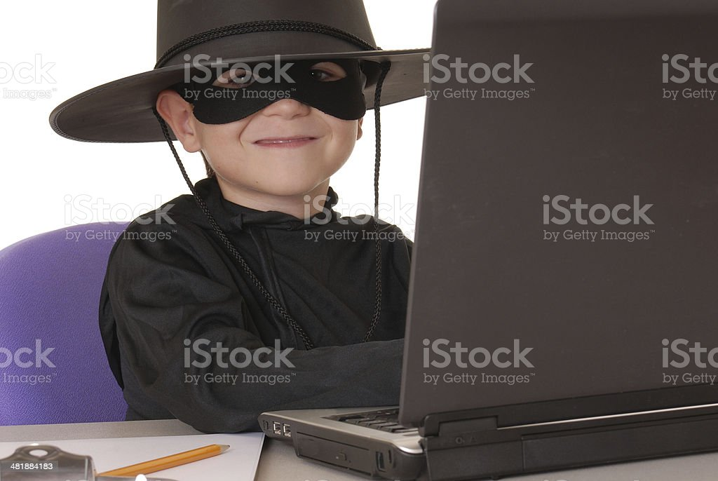 Child as costumed Zorro at laptop helpdesk royalty-free stock photo