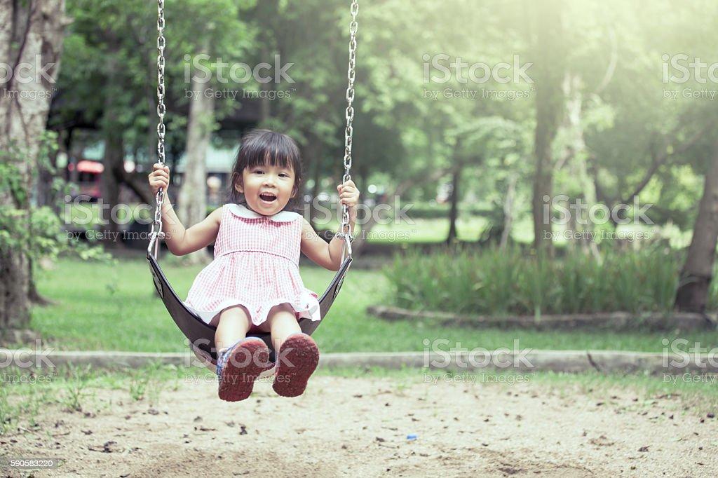 Child asian girl having fun to play swing in playground stock photo