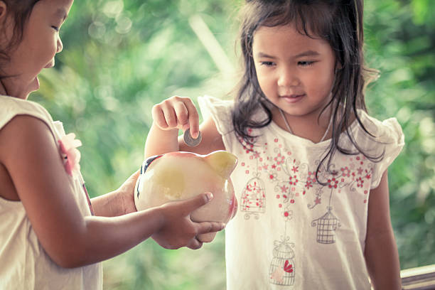Child asian little girl putting coin into Piggy Bank stock photo