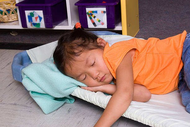 Child asleep on cot at daycare stock photo