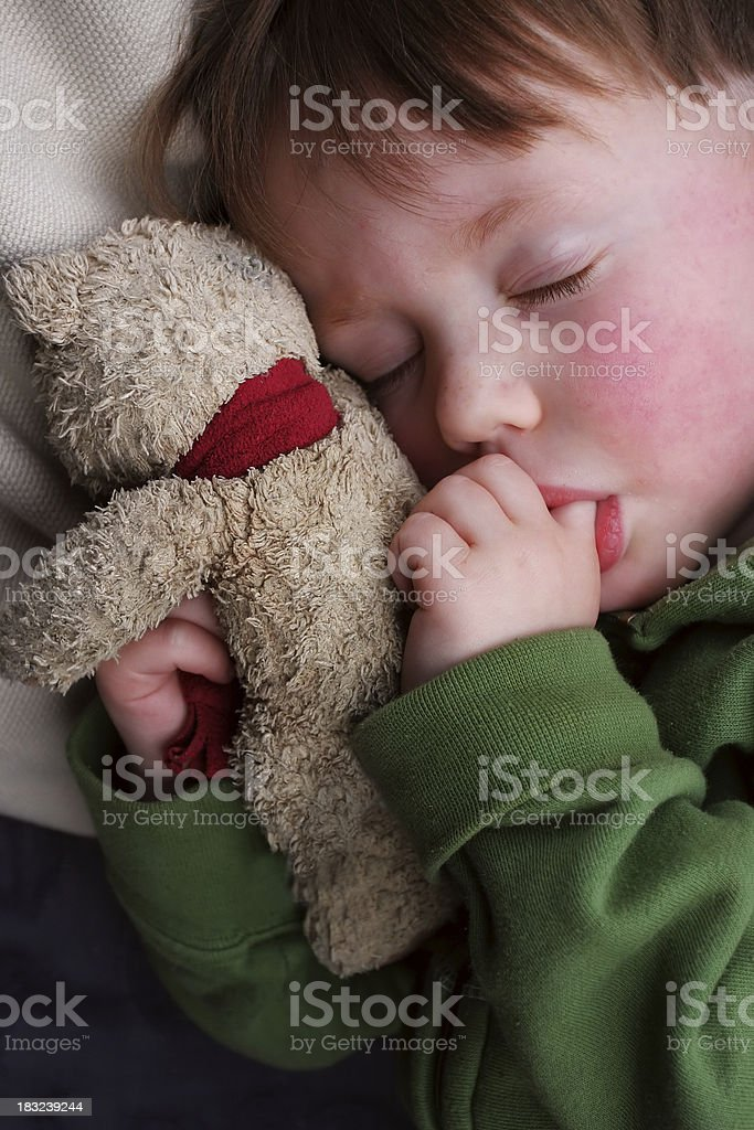 Child asleep with teddy bear, with thumb in mouth stock photo