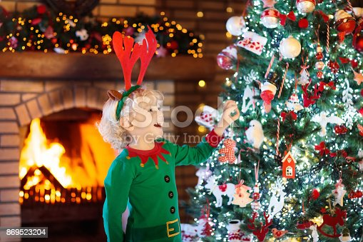 istock Child at Christmas tree and fireplace on Xmas eve 869523204