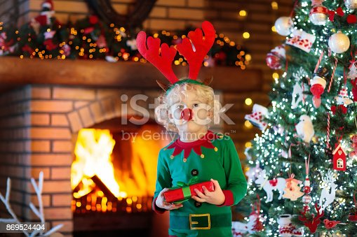 885695138 istock photo Child at Christmas tree and fireplace on Xmas eve 869524404