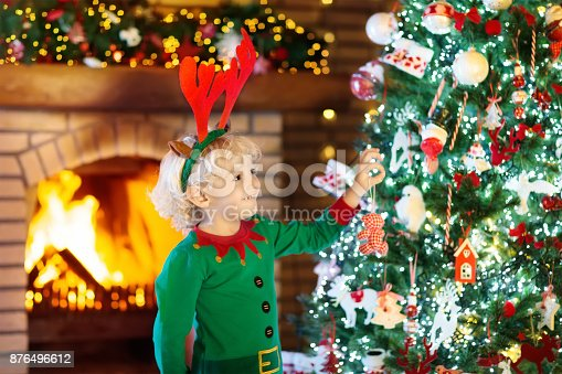 885695138 istock photo Child at Christmas tree and fireplace on Xmas eve 876496612