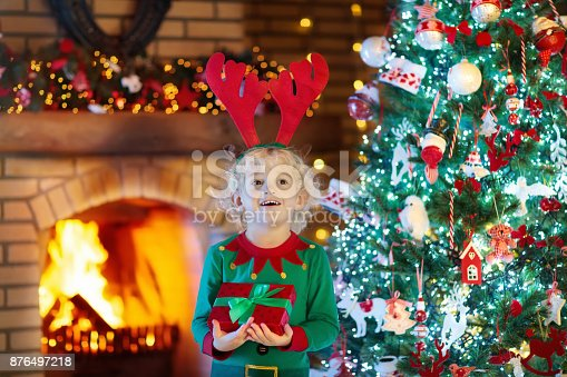 885695138 istock photo Child at Christmas tree and fireplace on Xmas eve 876497218