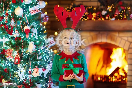 istock Child at Christmas tree and fireplace on Xmas eve 877877108
