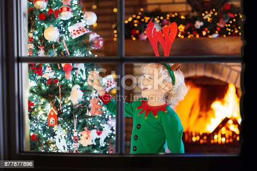 885695138 istock photo Child at Christmas tree and fireplace on Xmas eve 877877896
