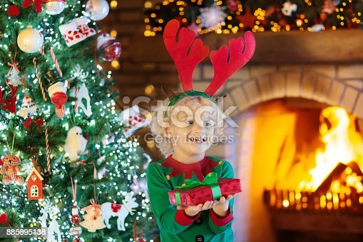 885695138 istock photo Child at Christmas tree and fireplace on Xmas eve 885695138