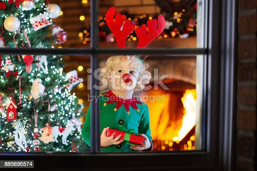 885695138 istock photo Child at Christmas tree and fireplace on Xmas eve 885695574