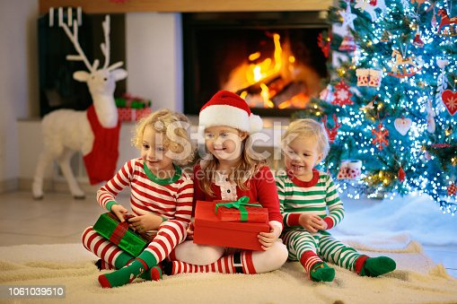 1068864298 istock photo Child at Christmas tree. Kids at fireplace on Xmas 1061039510