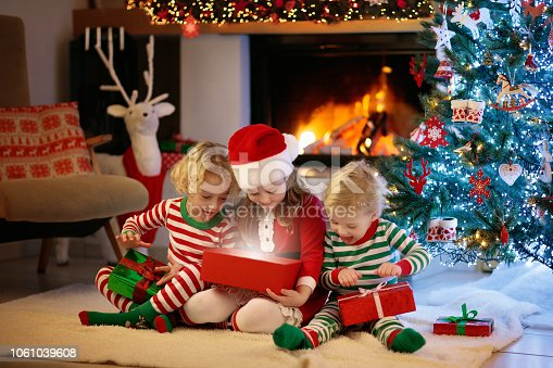 1068864298 istock photo Child at Christmas tree. Kids at fireplace on Xmas 1061039608