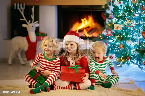 1068864298 istock photo Child at Christmas tree. Kids at fireplace on Xmas 1061048684