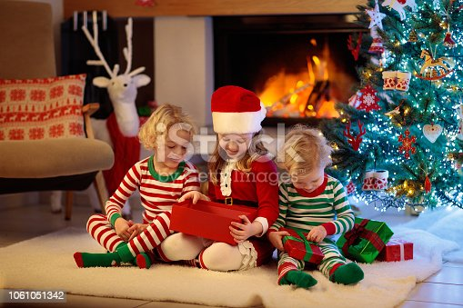 1068864298 istock photo Child at Christmas tree. Kids at fireplace on Xmas 1061051342