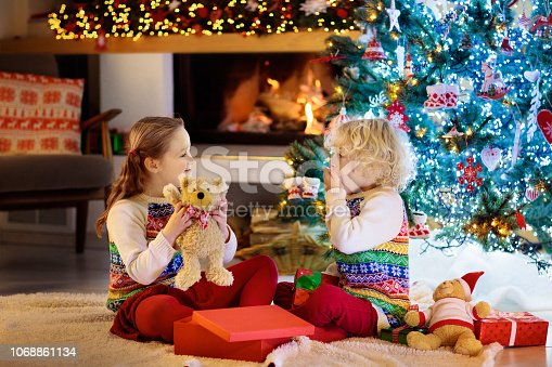 1068864298 istock photo Child at Christmas tree. Kids at fireplace on Xmas 1068861134