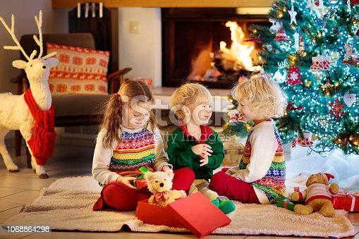 1068864298 istock photo Child at Christmas tree. Kids at fireplace on Xmas 1068864298