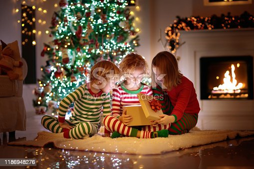 869520896 istock photo Child at Christmas tree. Kids at fireplace on Xmas 1186948276