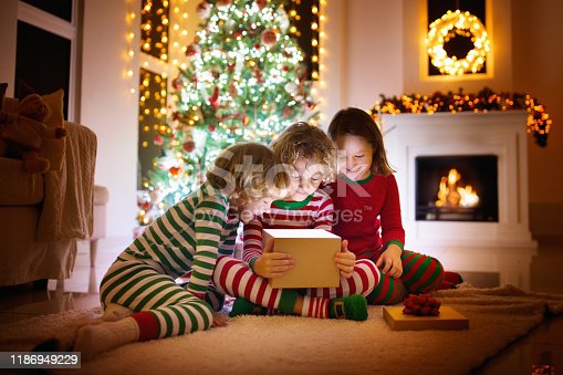 869520896 istock photo Child at Christmas tree. Kids at fireplace on Xmas 1186949229