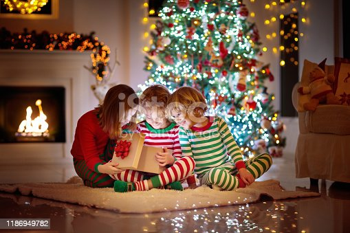 1068864298 istock photo Child at Christmas tree. Kids at fireplace on Xmas 1186949782