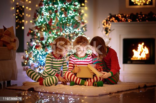 1068864298 istock photo Child at Christmas tree. Kids at fireplace on Xmas 1192366676