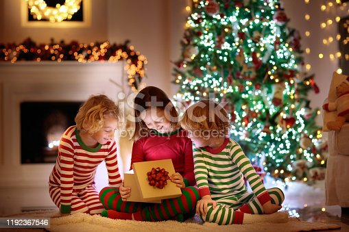 1068864298 istock photo Child at Christmas tree. Kids at fireplace on Xmas 1192367546