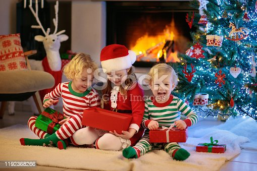 1068864298 istock photo Child at Christmas tree. Kids at fireplace on Xmas 1192368266