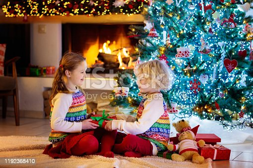 1068864298 istock photo Child at Christmas tree. Kids at fireplace on Xmas 1192368410