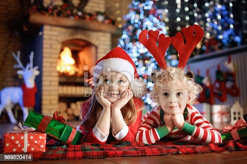 885695138 istock photo Child at Christmas tree. Kids at fireplace on Xmas 869520414